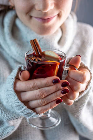 A woman in a white warm sweater is holding a transparent glass cup of mulled wine in her hand. Concept of a cozy atmosphere and a traditional winter drink.