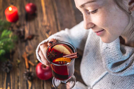 Girl in a warm sweater is holding a glass of mulled wine. Concept of a festive mood, a magical cozy atmosphere with a mug of traditional hot beverage. Stock fotó