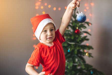 Cute little child in a Santa hat is holding a Christmas ball in his hand on the background of a decorated Christmas tree with garlands.