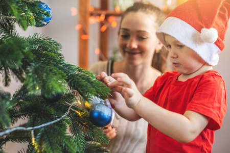 Mother with her child son is decorating the Christmas tree with toys and Christmas balls. Happy family time on new year's eve at home