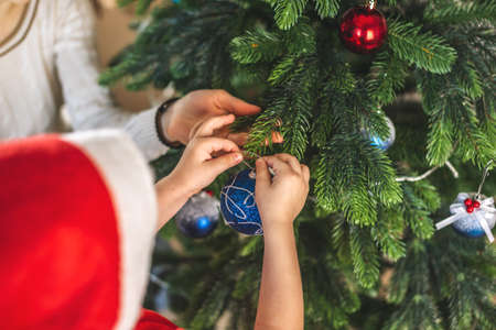 Mother and her child son are holding a Christmas tree ball toy to hang on a branch. The concept of a happy loving family on new year's eve