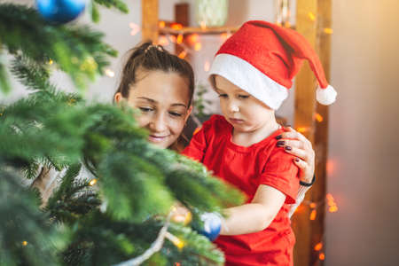 Mother with her child son is decorating the Christmas tree with toys and Christmas balls. Concept of a happy loving family on new year's eve