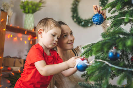 Mom is helping her child son decorate the Christmas tree with toys and Christmas balls. The concept of a happy loving family on new year's eve