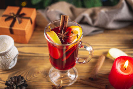 Cup of aromatic hot mulled wine on a wooden table. Concept of a festive atmosphere and traditional winter beverage.