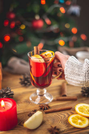 A woman's hand in a warm sweater is holding a cup of aromatic hot mulled wine against the background of a Christmas tree with lights. Concept of a festive atmosphere.