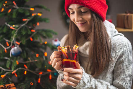 Woman in a warm sweater is drinking aromatic hot mulled wine on the background of a Christmas tree with lights. Concept of a holiday atmosphere and cozy winter mood.