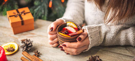 Woman's hands in a warm sweater are holding a cup of aromatic hot mulled wine on a wooden table. Concept of a festive atmosphere and cozy winter mood.