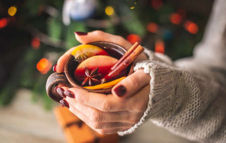Woman in a warm sweater is holding in her hands a cup of aromatic hot mulled wine on the background of a Christmas tree with lights. Concept of a festive atmosphere and cozy winter mood. Closeup