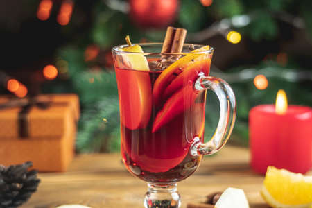 Cup of aromatic hot mulled wine on a wooden table on the background of a Christmas tree with lights. Concept of a festive atmosphere.