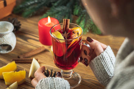 Woman in a warm sweater is holding a cup of aromatic hot mulled wine in her hands on a wooden table. Concept of festive and cozy atmosphere.
