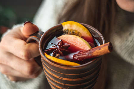 Woman in a warm sweater is drinking aromatic hot mulled wine. Concept of a holiday atmosphere and cozy winter mood. Closeup.