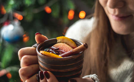Woman in a warm sweater is holding a cup of aromatic hot mulled wine on the background of a Christmas tree with lights. Concept of a holiday atmosphere and cozy winter mood. Stock fotó