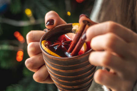 A woman's hand is holding a cup of aromatic hot mulled wine against the background of a Christmas tree with lights. Concept of a festive atmosphere.