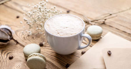 Cup of aromatic coffee and macaroons and an envelope on a wooden table. Concept of a cozy atmosphere and nice breakfast.
