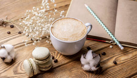 Cup of aromatic coffee, macaroons and a notebook on a wooden table. Concept of a nice coffee break and lifestyle