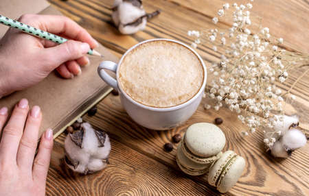 A woman's hand is writing something in a notebook and near a cup of coffee and macaroons. Concept of a cozy breakfast or coffee break.