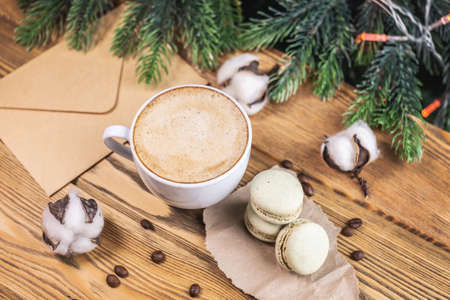 Cup of aromatic coffee and macaroons and an envelope on a wooden table on the background of a Christmas tree. Concept of a cozy atmosphere. Stock fotó