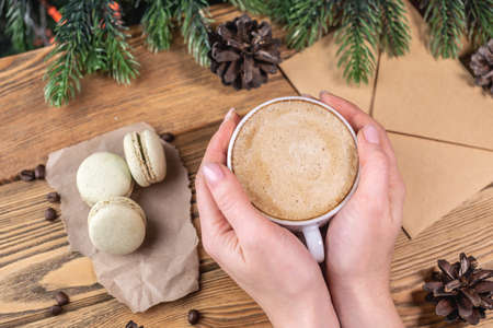 Women's hands are holding a cup of coffee and next to it on a wooden table macaroons and an envelope on the background of a Christmas tree. Concept of a cozy atmosphere.