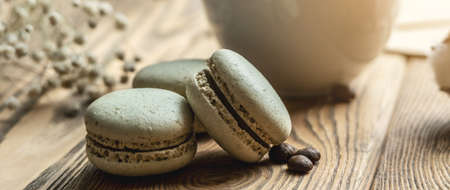 Delicious pastel green macaroons and a white cup with a beverage on a wooden table closeup.