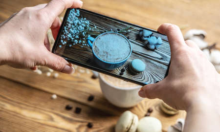 A woman's hands are holding a mobile phone and taking photos breakfast of coffee and macaroons on a wooden background.