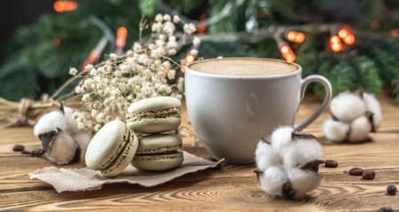 Cup of coffee with macaroons on a wooden table with a Christmas tree background. Concept of a cozy festive atmosphere and mood of the winter.