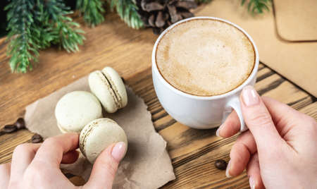A woman's hands are holding a delicious green pastel macaroon and cup of coffee on a wooden background. Stock fotó