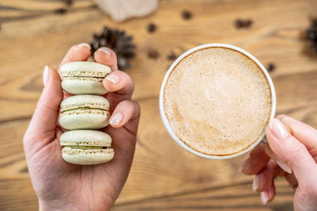 A woman's hands are holding a stack of delicious green pastel macaroons and cup of coffee on a wooden background.