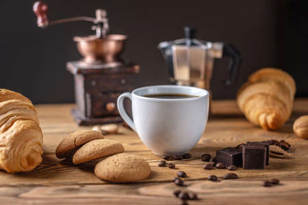 There is hot black coffee with croissants, cookies and chocolate on a wooden table. There is a coffee grinder and a geyser coffee maker In the background.