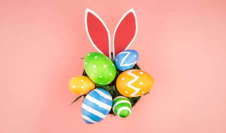 Bright Easter colorful eggs, paper rabbit ears on a pink background. Top view.