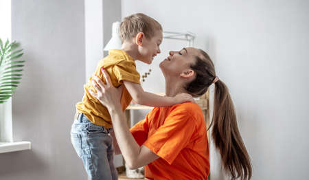 Mother and child wearing in bright clothes are tenderly hugging each other. Concept of a happy harmonious family, caring and pastime with children.