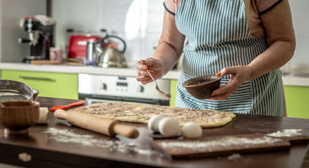 Woman is sprinkling cinnamon on raw dough to make fragrant homemade buns. Concept of the cooking process of baking. Stock fotó