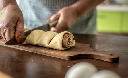 Woman in an apron in the kitchen is gently cutting fresh raw dough with a knife to make delicious homemade cinnamon rolls. Concept of the cooking process of baking.
