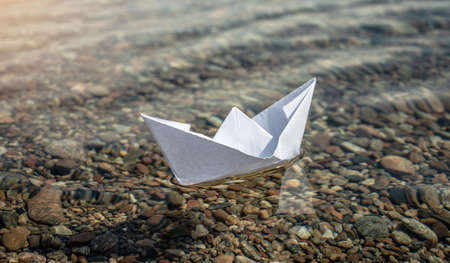 White paper boat in the clear water of large lake with a stony bottom.