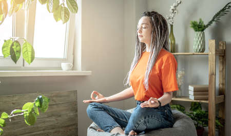 Modern young woman is sitting in a baggy chair in the morning at home and meditating. Concept of harmony, calmness and lifestyle. Stock fotó
