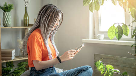 Young modern woman is sitting on a chair at home and using a tablet to read the news or view other information. Concept of pastime, relaxation and lifestyle. Stock fotó