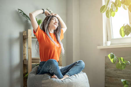 Young modern woman is sitting in a bag chair next to the window and stretching. Concept of morning, calm, mood. Stock fotó