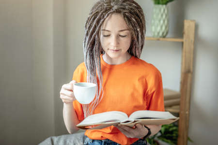 Modern young woman with a cup of coffee or tea and bright clothes is sitting and reading a book at home. Concept of leisure, pastime, learning and lifestyle.