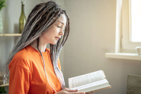 Young woman with dreadlocks and bright clothes is sitting and reading a book at home. Concept of leisure, pastime, learning and lifestyle.