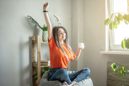 Young modern woman with a cup of coffee is sitting in a bag chair next to the window and stretching. Concept of morning, calm, mood. Stock fotó
