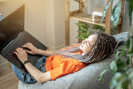 Young modern woman with dreadlocks is comfortably sitting in a chair bag at home and using a laptop for work, study or leisure. Concept of pastime, lifestyle and comfortable remotely work. Stock fotó