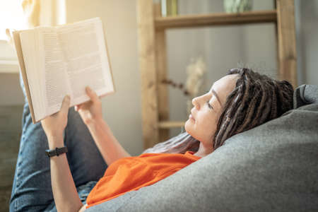 Young woman with dreadlocks and bright clothes is sitting comfortably in a bag chair and reading a book. Concept of leisure, pastime, learning and lifestyle.