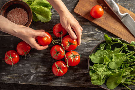 Woman's hands are tearing a ripe red tomato from a branch. On the black table are tomatoes, arugula, green salad and a cutting board for cooking a light summer vegetable salad. Top view. Stock fotó