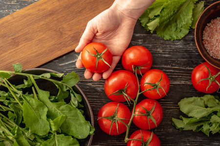 Woman's hand is holding a ripe red tomato. On the black table are tomatoes, arugula, green salad and a cutting board for cooking a light vitamin vegetable salad. Top view.