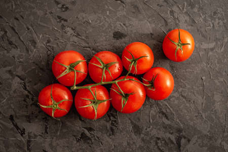Whole ripe red tomatoes on a branch on a black background. Top view.