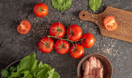 There are tomatoes, arugula, green salad and a cutting board for cooking a light healthy vegetable salad on the black background. Top view. Stock fotó