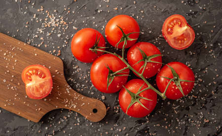 Whole ripe red tomatoes on a branch, a sliced tomato and a cutting board on a black background. Top view.