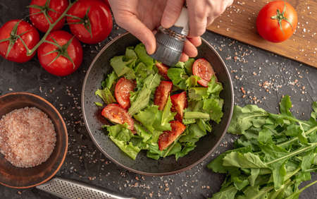 Women's hands are sprinkling a light vitamin vegetable salad with spices. Concept of cooking healthy food. Top view and dark background.