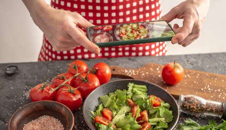 Women's hands are holding a mobile phone over a beautiful appetizing vegetable salad to take a photo. Stock fotó