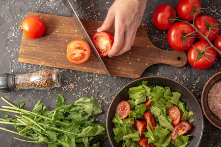Women's hands are cutting a ripe tomato to cook a light healthy vegetable salad with tomatoes and arugula. Black background and top view.