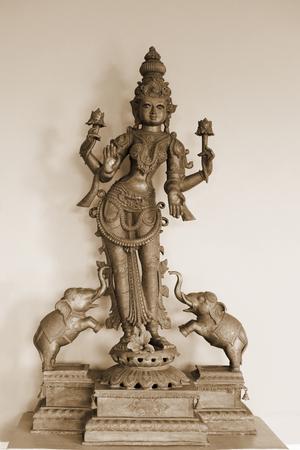 Golden Hindu Goddess Kali isolated on a white wall background Stock Photo